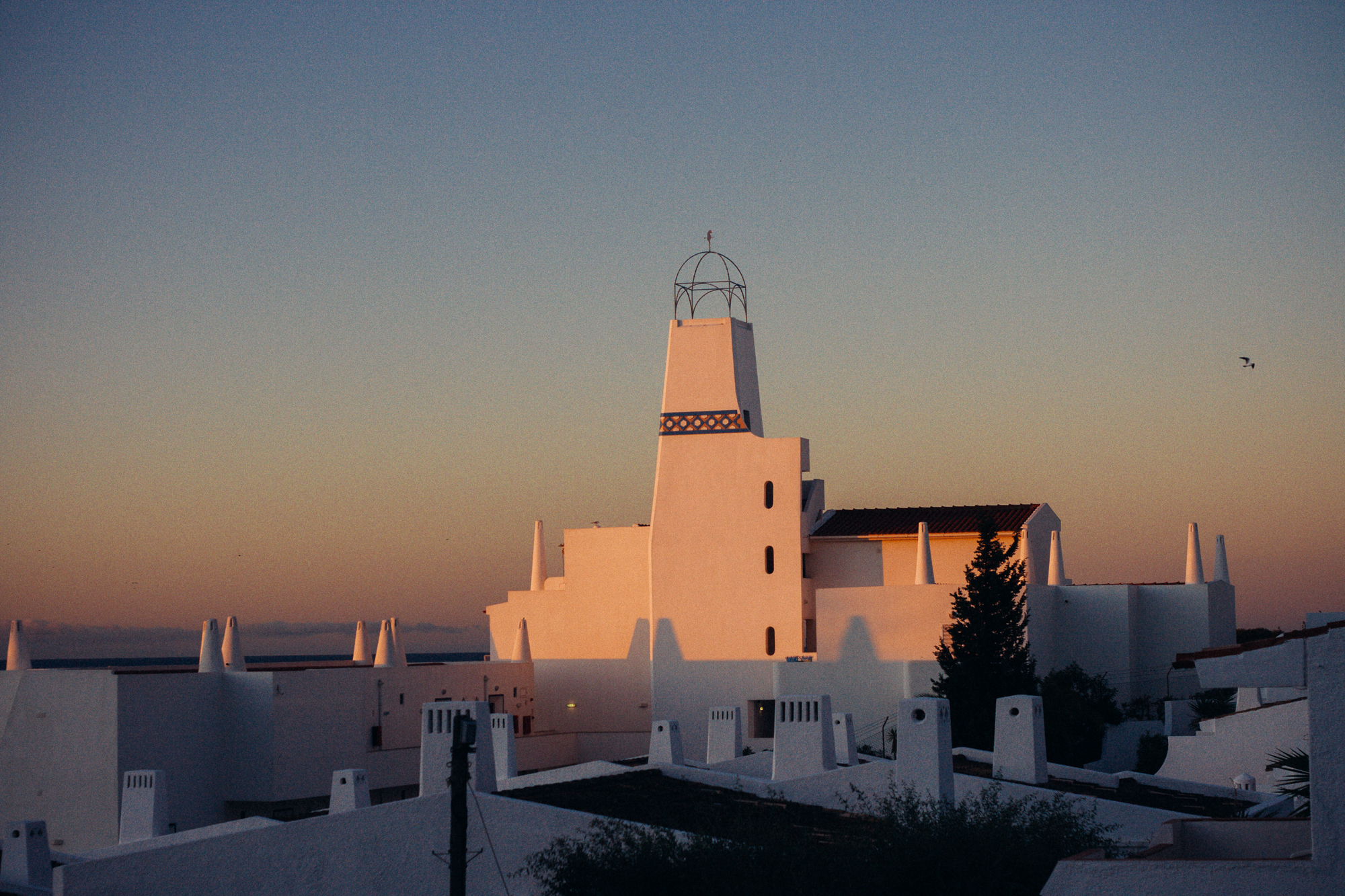 white buildings in portugal lit by the sunset. by leonie wise