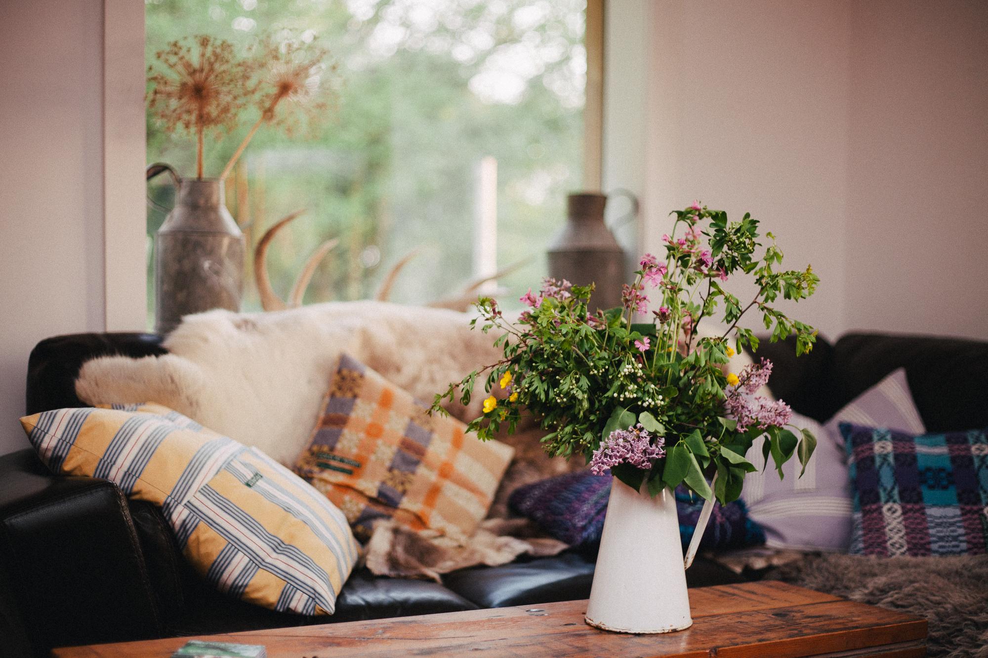 Wildflowers in enamel jug with sofa in background. By Leonie Wise