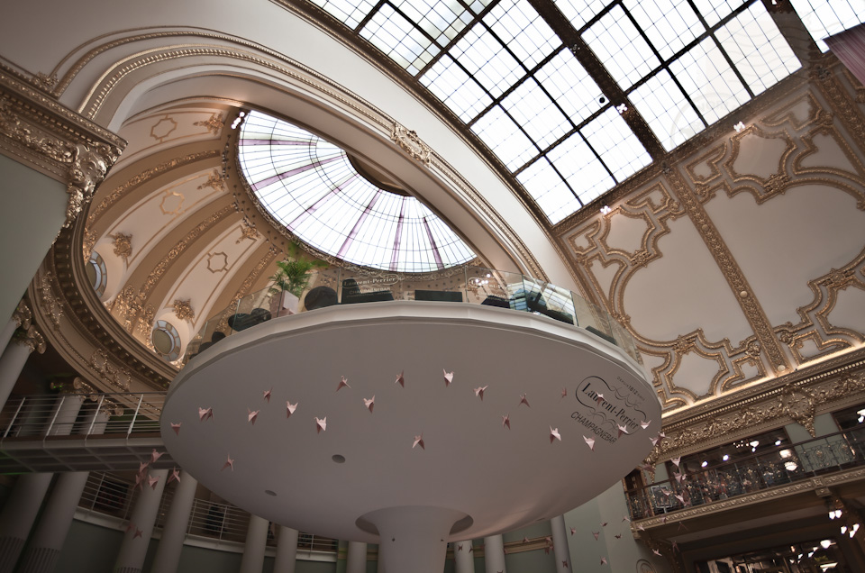 "The ""floating terrace"" of the only Laurent Perrier champagne bar in the world offers from its 7.7 metres height a magnificent view over the brightly renovated architecture of the Stadsfeestzaal Shopping in Antwerp."