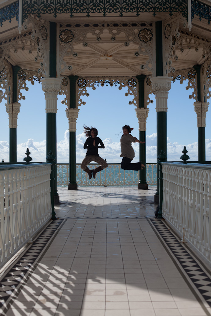 kristen perman and leonie wise doing a jump shot at the brighton pavilion on the brighton waterfront
