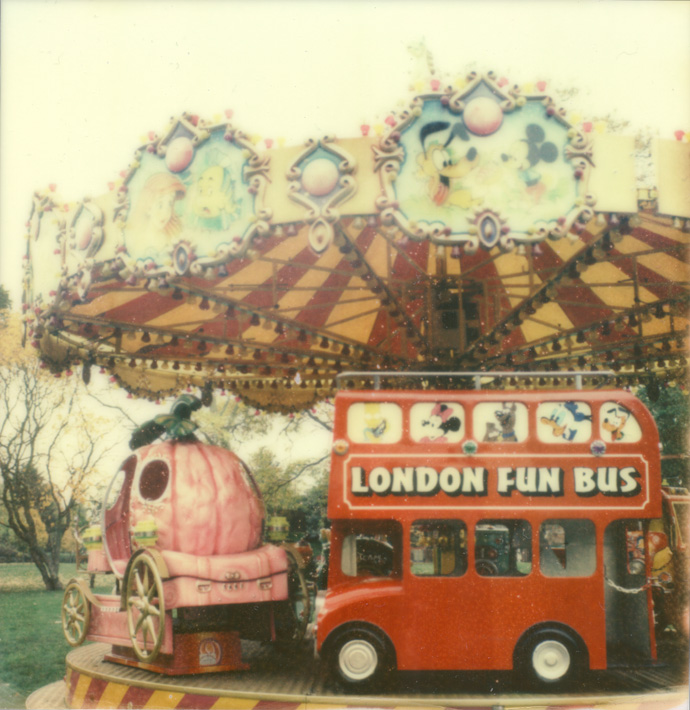 polaroid of a childrens carousel in a park with a big red bus in the foreground of the carousel. copyright leonie wise