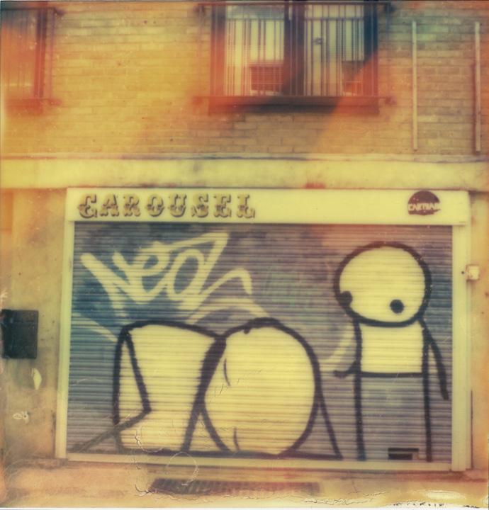 polaroid photograph of stickman street art on the carousel roller door. copyright leonie wise