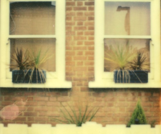 polaroid photograph of two windows and the top of a picket fence. copyright leonie wise
