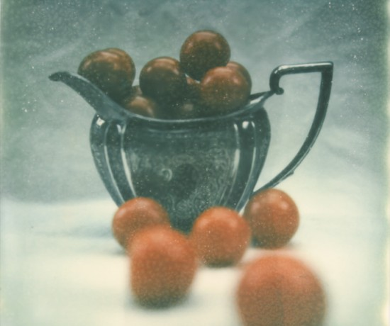 polaroid photograph of small tomatoes in a silver jug. copyright leonie wise