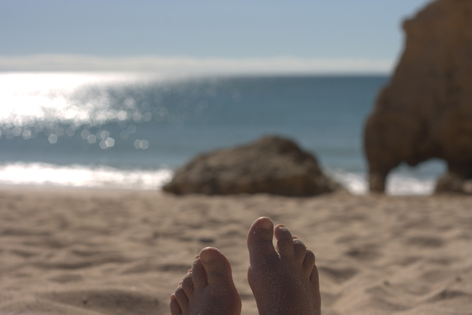 sandy feet on a sunny beach in portugal. copyright leonie wise