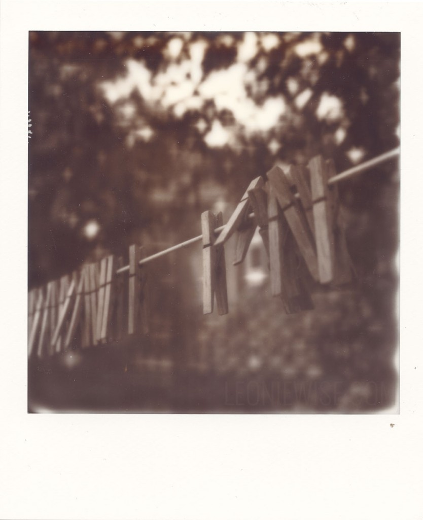 polaroid photograph of pegs on a line