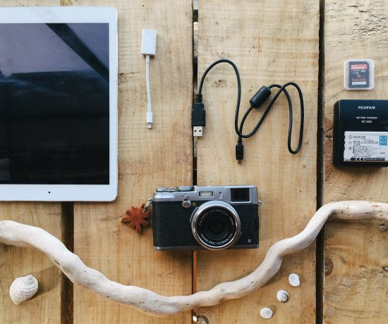 Fuji x100s camera, Ipad, Battery Charger, Memory cards and USB cable on a table. By leonie wise