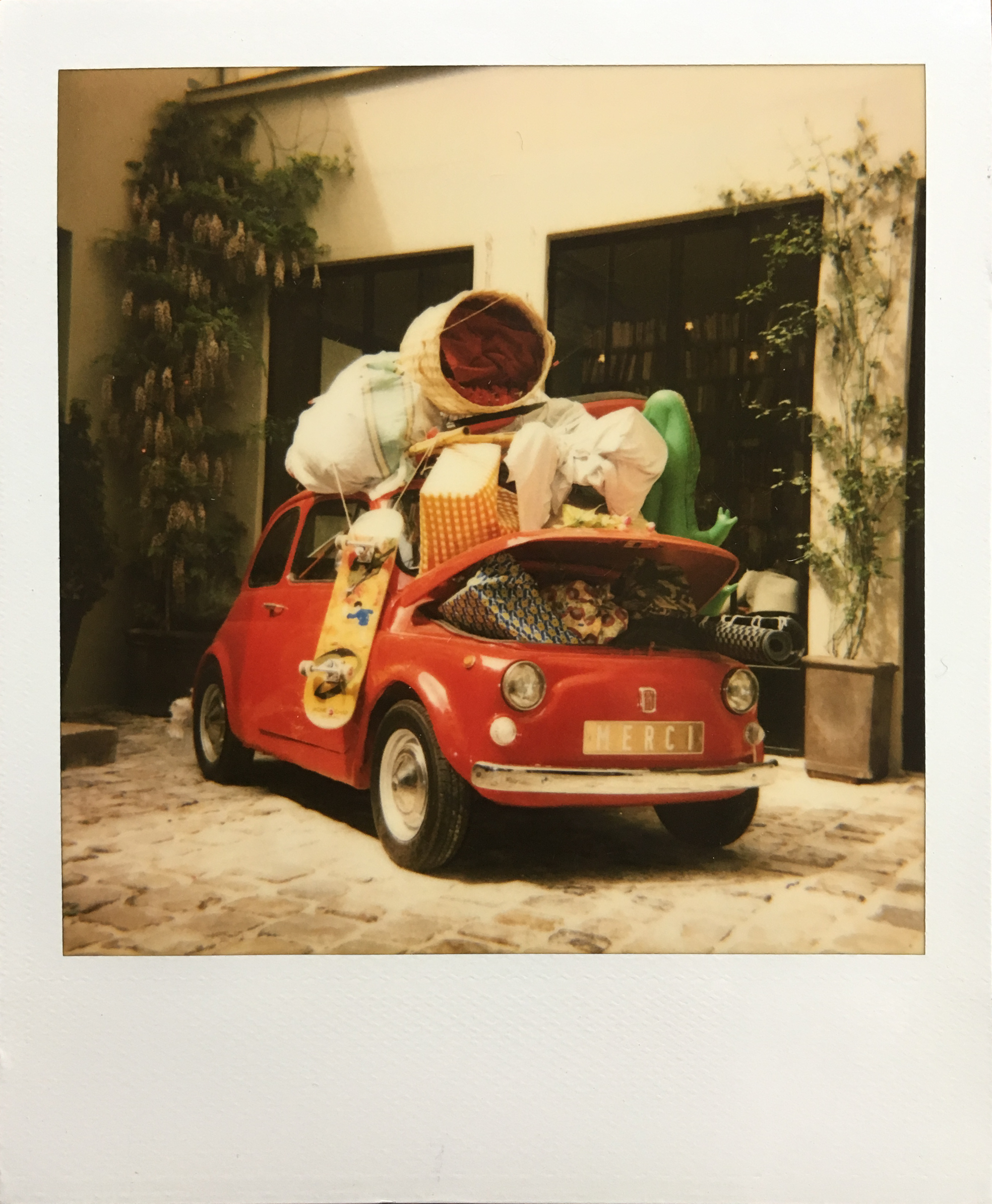 Little Bambina Car loaded with stuff outside Merci Paris. Polaroid sun600. By Leonie Wise