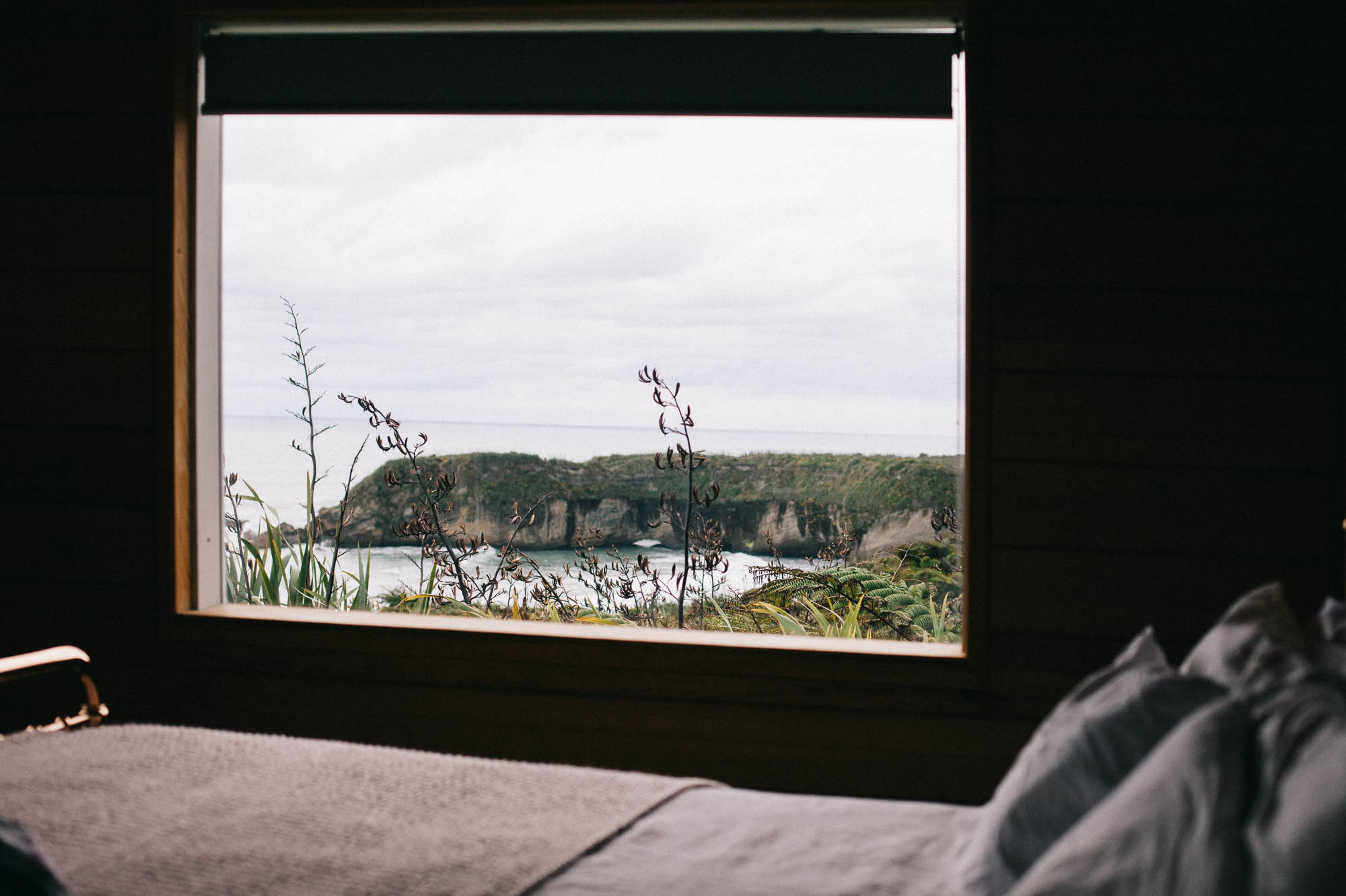 Bed and window with a view down to the bay below at Woodpecker Hut (c) Leonie Wise