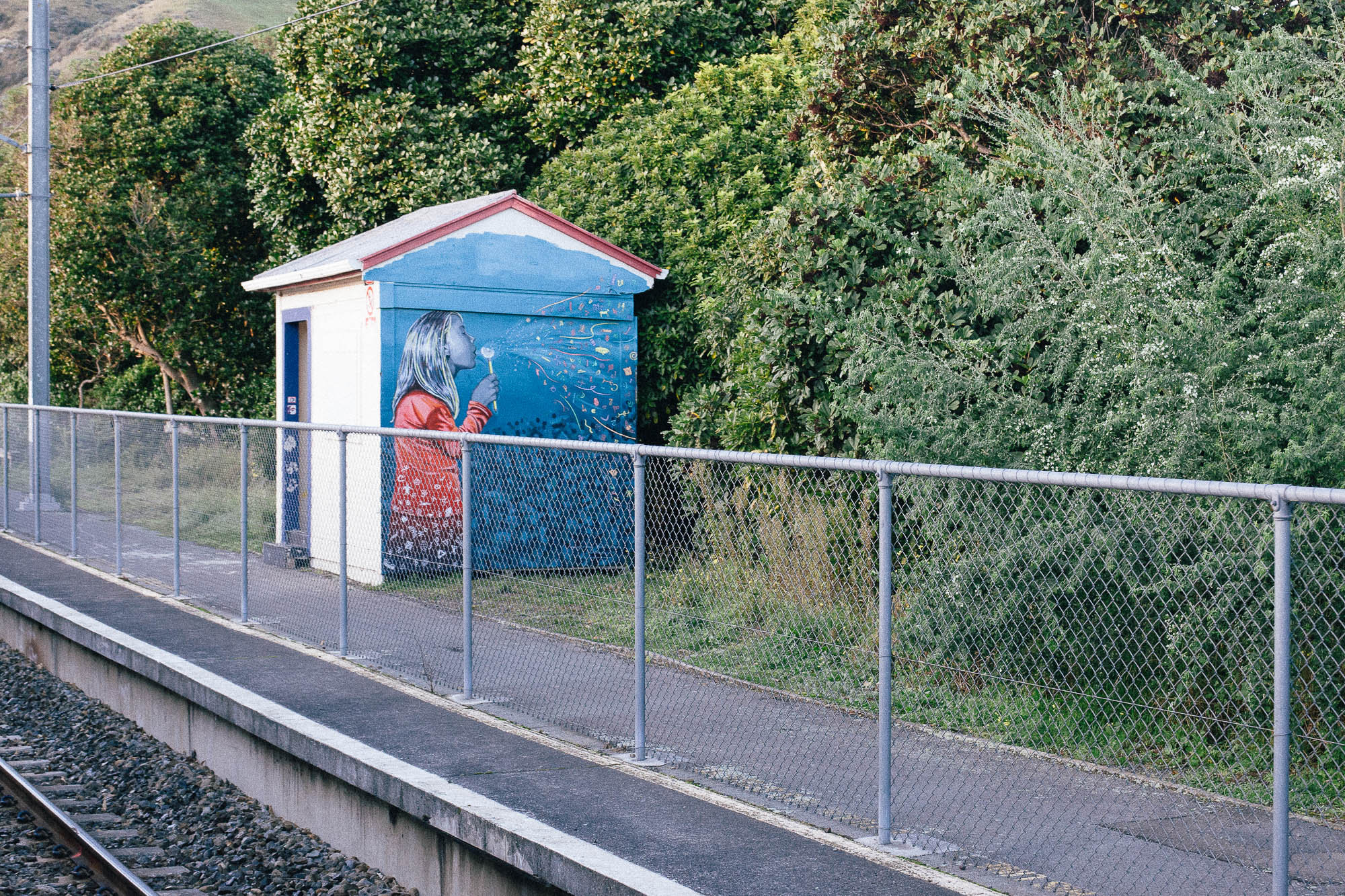 a moment unravelling time: a mural of a girl blowing a dandelion clock on the wall of a building beside a railway line. (c) leonie wise