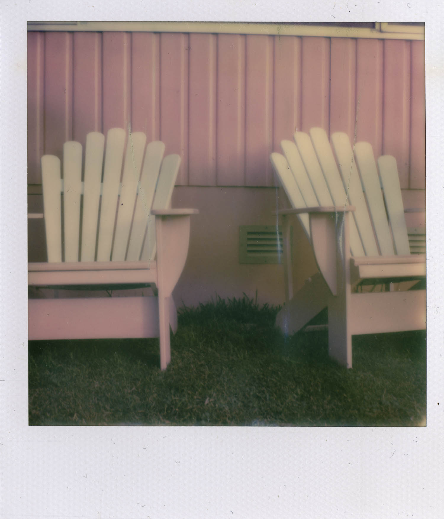 photograph of pink weatherboard on the side of a house with two pink and white adirondack-style chairs on the grass in front of the building. © leonie wise